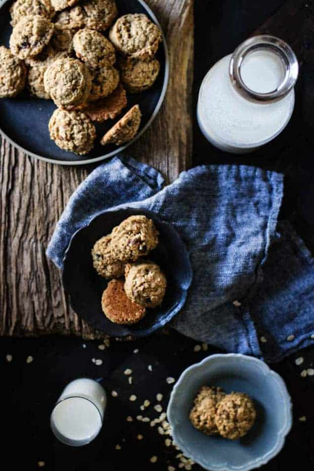 3 bowls piled high with oatmeal date cookies are sitting on a wooden table. There is a large glass jug and a small glass full of milk and a linen napkin also on the table.