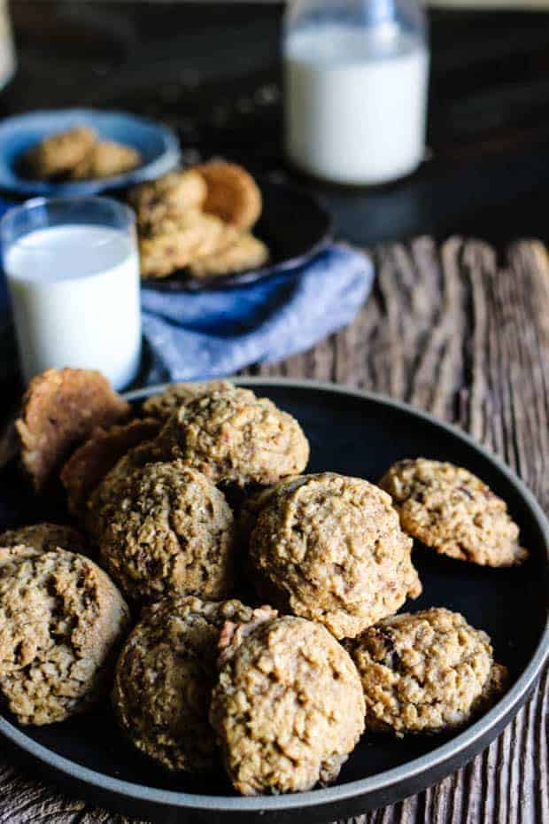 A pile of Gluten Free Oatmeal Date Cookies on a black plate. There is a small glass and a large glass bottle of milk another small bowl filled with cookies and a linen napkin in the background.