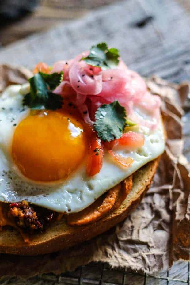 A close up image of hummus toast on a piece of brown butcher paper. On top of the slice of toasted sourdough is hummus, walnut taco crumbles, a perfectly fried egg, pico de gallo, cilantro, and pickled red onions