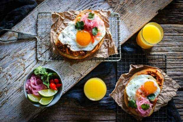 A wooden table top is set with a breakfast scene. 2 glasses of orange juice, 2 small, personal, wire baking wracks with handles each have a large slice of hummus toast on top. There is also a small bowl of garnishes; lime wedges, red pickled peppers, pickled red onions, cilantro leaves.