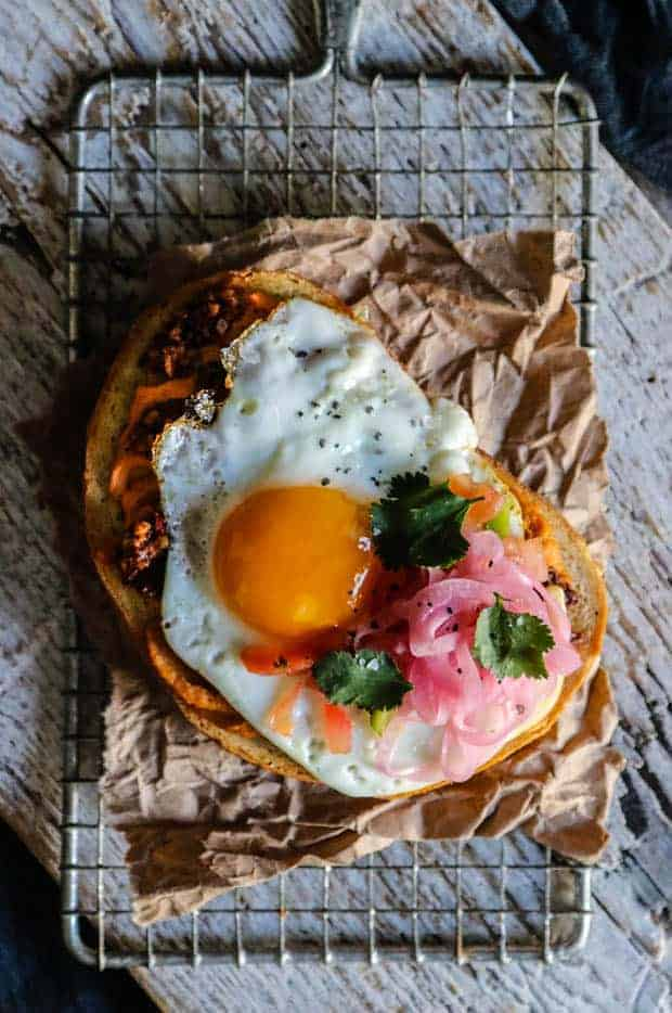 A large, thick piece of toasted sourdough is topped with hummus, walnut taco crumbles, a fried egg, pico de gallo, and pickled red onions.