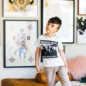 a cute little brown haired boy in tan skinny jeans and a black and white Beastie Boys t-shirt stands in front of a wall full of framed street art.