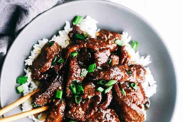 A gray bowl is filled with white rice and topped with Mongolian beef and scallions.