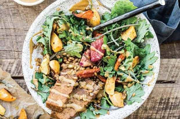 A white bowl filled with greens, tempeh bacon strips, roasted sweet potatoes, and drizzle din a maple mustard dressing