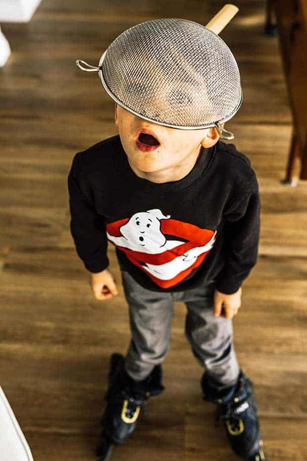 A little boy on roller blades wearing a Ghost Busters sweat shirt . He has a metal kitchen strainer on his head like a hat.