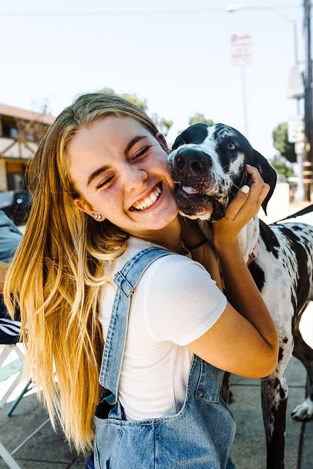 Girl in a blue jean overall dress with a white t-shirt underneath and blonde hair is hugging a black and white spotted great dane.