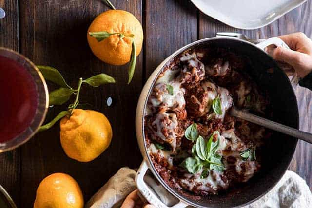 a large dutch oven filled with meatballs and tomato sauce topped with green herbs is sitting on a table with a plate, napkin, and a bunch of citrus fruit