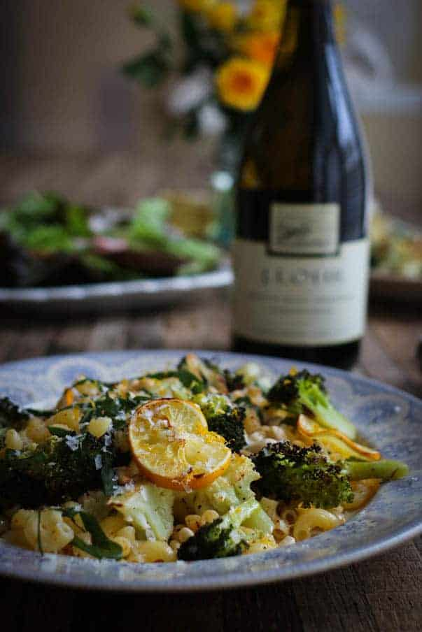 A bottle of chardonnay is sitting on a wooden table top. There is a big platter filled with a hearty green salad behind it and a big bowl of pasta mixed with a brown butter sauce, roasted Meyer lemon wheels, broccoli, & cauliflower