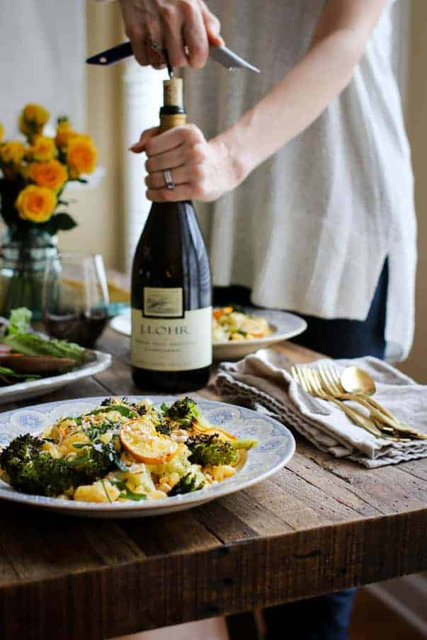 A woman in a white shirt is opening a bottle of J Lohr chardonnay. She is standing behind a table that has two plates of pasta, a blue mason jar filled with yellow roses, and a big salad.