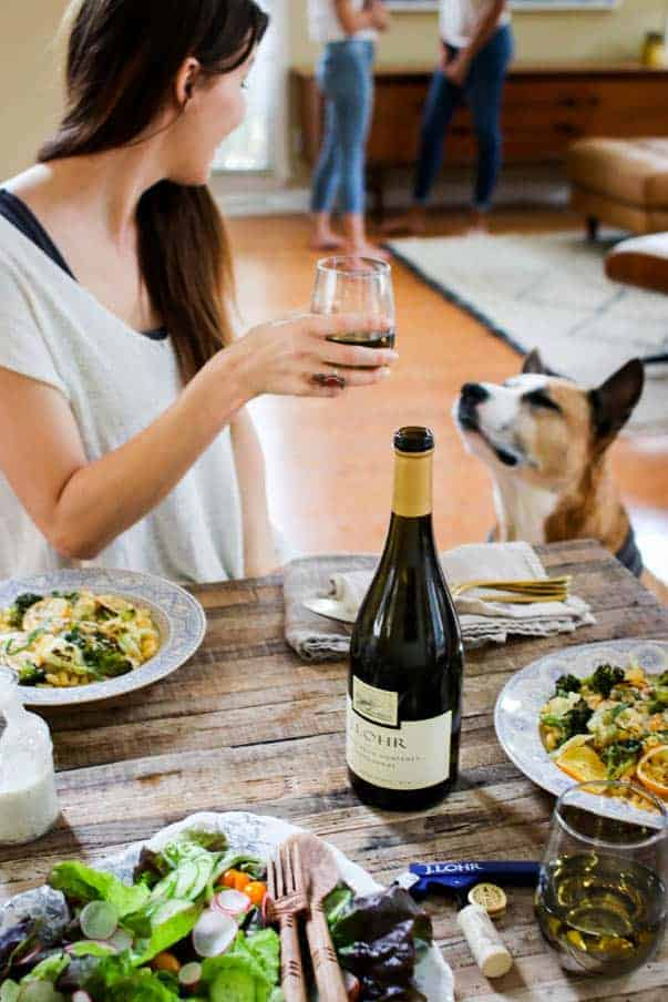 A woman is sitting at table that is set with 2 plates of pasta, a big salad, and a bottle of chardonnay. She is looking at her dog and her dog is looking back at her. There are 2 women in the background.