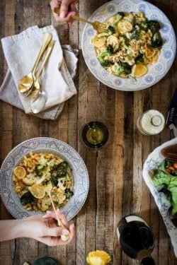 2 vintage white plates with blue rims are loaded with Roasted Meyer Lemon and Brown Butter Pasta . There is a bottle of chardonnay on the table, a pile of linen napkins and gold forks, and a big salad.