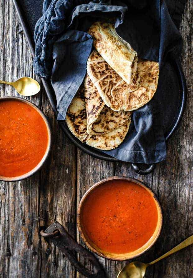 2 bowls of tomato soup on a wooden table top with a basket of grain free naan wrapped in a black linen towel