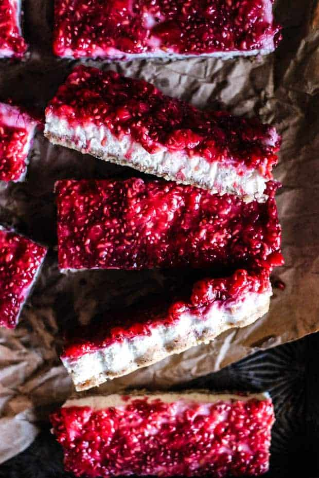 5 rectangular bars with a nut flour crust, coconut butter layer, and a raspberry chia jam layer. The bars are laid out on a piece of brown parchment.