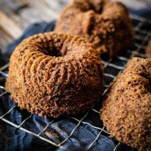 3 mini bundt cakes on a mesh cooling rack sits over a black linen cloth.