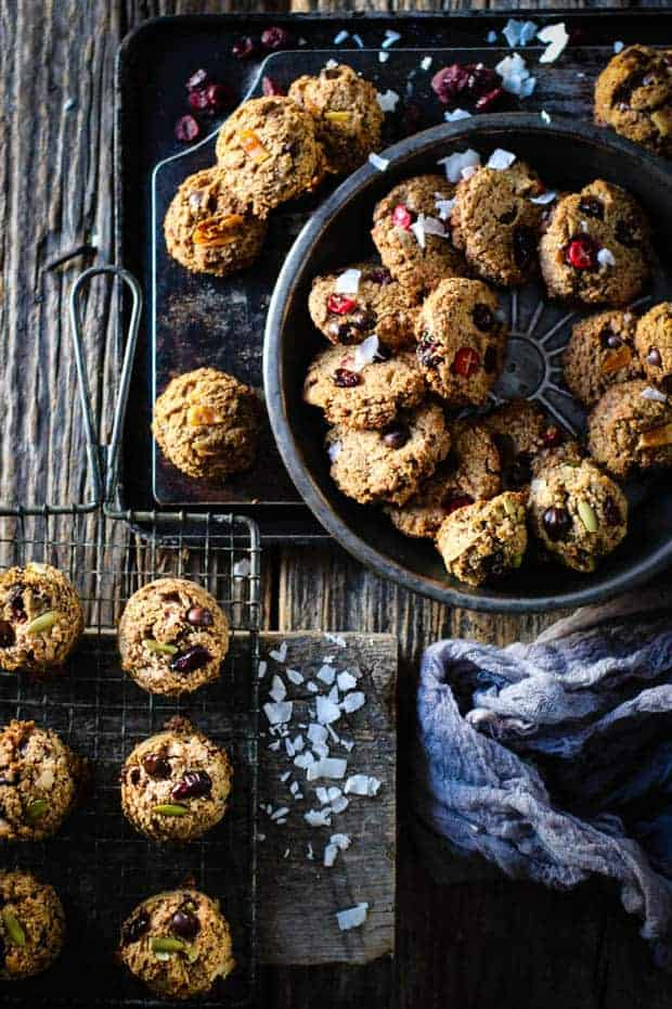 3 different types of kitchen sink cookies arranged in metal bowls an pans on a table top. . There are also coconut flakes and craisins scattered across the tops of the cookies.