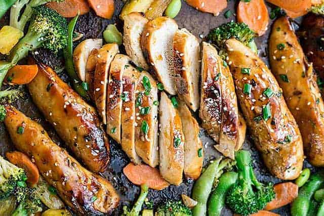 A sheet pan is filled with sliced 4 sliced teriyaki chicken breasts and has broccoli, slice carrots, and pineapple around the chicken.
