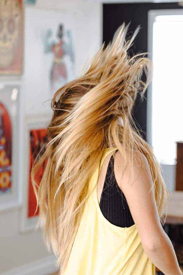 A girl with long blonde hair in a yellow tank top is dancing wildly. Her hair is all around her face so you cannot see it. There is colorful art on the wall behind her