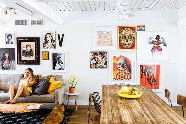A girl with blonde hair in a yellow tank top sits on a grey couch in a modern house. there is lots of colorful art ob the walls, a live edge wood coffee table and a black and white rug.