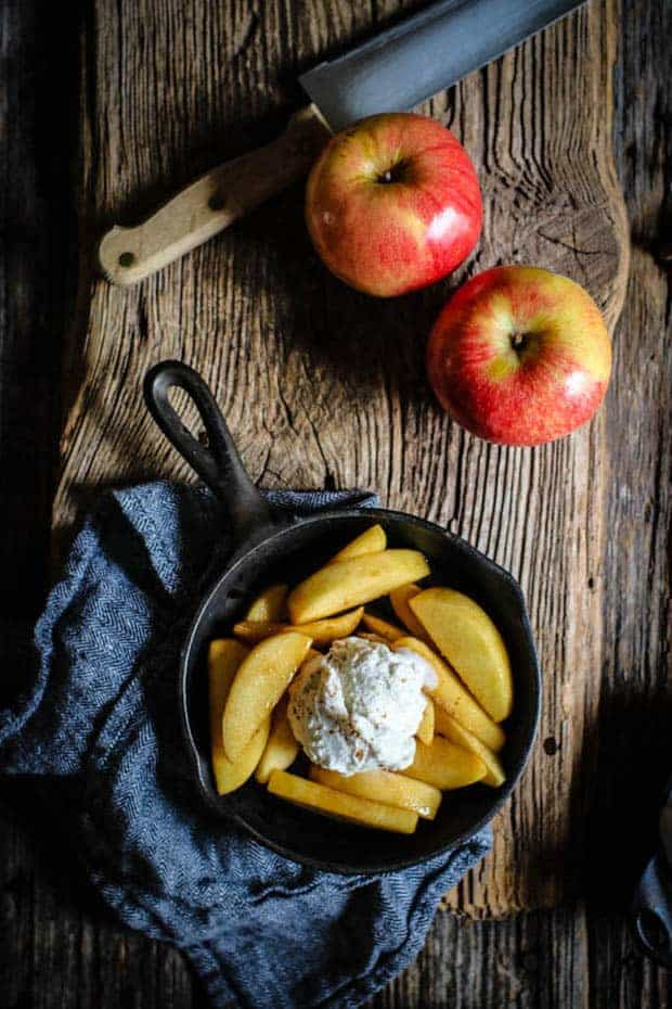 a small cast iron skillet filled with vanilla scented fried apples and a large scoop of vanilla bean ice cream. There are 2 red apples on the table next to the skillet and teh skillet is on a herringbone napkin.