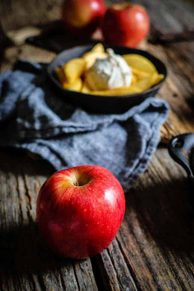 A bright red Stemilt Piñata apple sits on a wooden table top infant of a small cast iron skillet that is filled with vanilla scented fried apples and a scoop of vanilla bean ice cream.