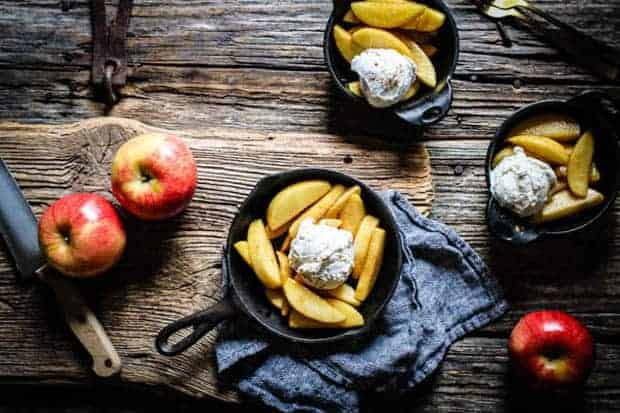 3 small cast iron pans filled with vanilla scented pan fried apples and scoops of ice cream sit on a wooden table top. There are 3 red apples on the table as well as a chefs knife. One of the skillets is resting on a herringbone napkin.