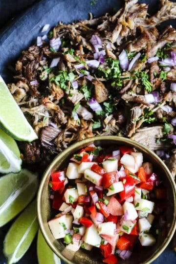 A gold bowl of apple salsa and a plate carnitas with lime wedges on the side and fresh red onions and cilantro on top.