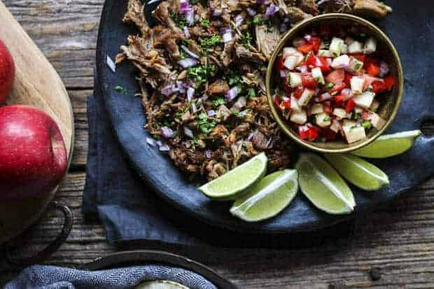 Instant Pot Carnitas garnished with chopped red onion and cilantro on a black plate with lime wedges and a bowl of apple salsa sit on a wooden table that also has a cutting board with whole apples on it.