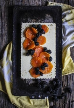 A white tart topped with fresh sliced oranges and blackberries sits on a black metal tray over a white and yellow linen napkin.