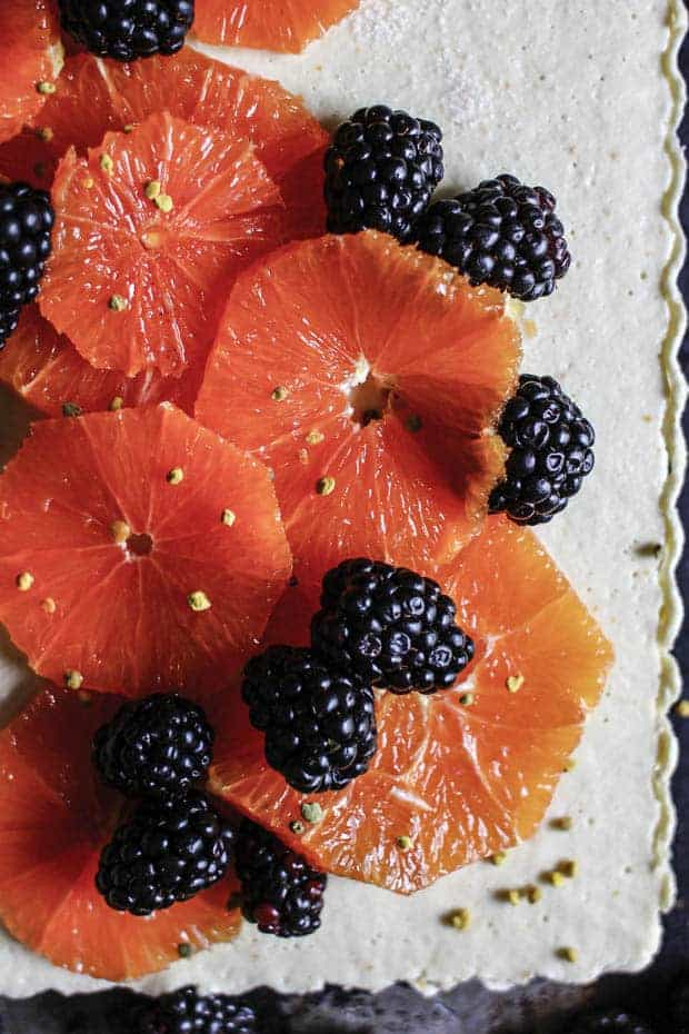A white tart with fluted edges topped with sliced, pink, Cara Cara oranges, blackberries, and a sprinkle of yellow bee pollen.