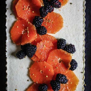A white tart topped with slices of orange and blackberries with a sprinkle of bee pollen.