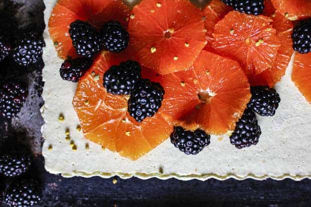 A horizontal image of a white tart with fluted edges topped with sliced, pink, Cara Cara oranges, blackberries, and a sprinkle of yellow bee pollen.