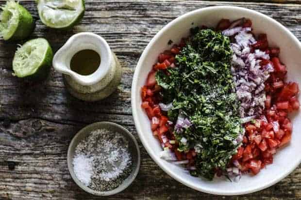 A shallow, white bowl filled with pico de gallo ingredients - layers pf finely diced tomatoes, red onion, jalapeño pepper, and cilantro. A small dish of coarse salt, a small ceramic pitcher of olive oil, and 3 squeezed lime halves are ob the table next to the bowl.