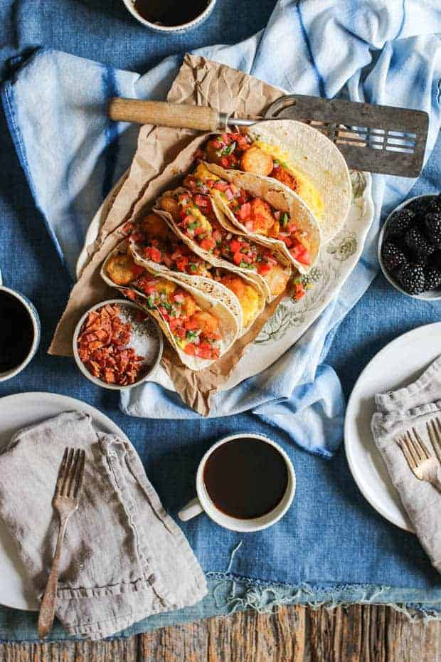A platter full of breakfast tacos is on a table that is covered in a denim table cloth. There is a blue and white napkin on the table underneath the platter of tacos, mugs of coffee, and a bowl of blackberries on the table.