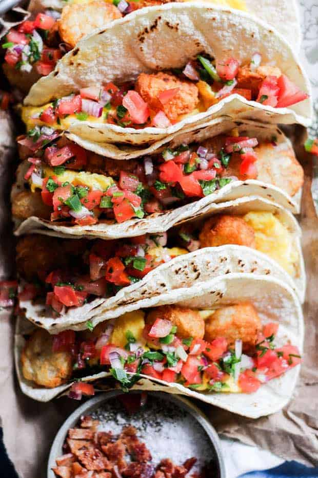 4 tacos, corn tortillas stuffed with scrambled eggs, tater tots, and pico de gallo. The tacos are arranged on a platter next to a bowl that has chopped bacon in it.