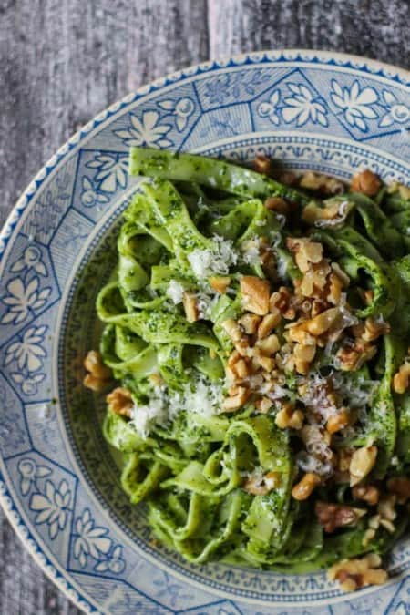 A close up image of a shallow blue and cream colored bowl filled with noodles coated in a bright green kale pesto. There are walnuts and grated cheese on top.