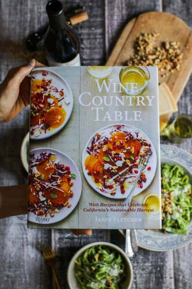 Janet Fletcher's new cookbook The Wine Country Table is being held over a table setting that is styled with walnut kale pesto pasta.