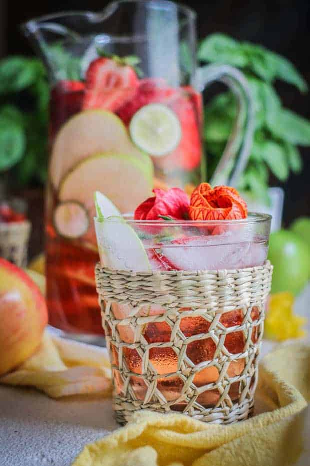 A clear cocktail glass with a woven ratan cover on it is filled with apple and strawberry slices, hibiscus blossoms, and apple and berry rosé sangria. Teh glass is in front of a large clear glass pitcher filled with the same fruits and beverage.