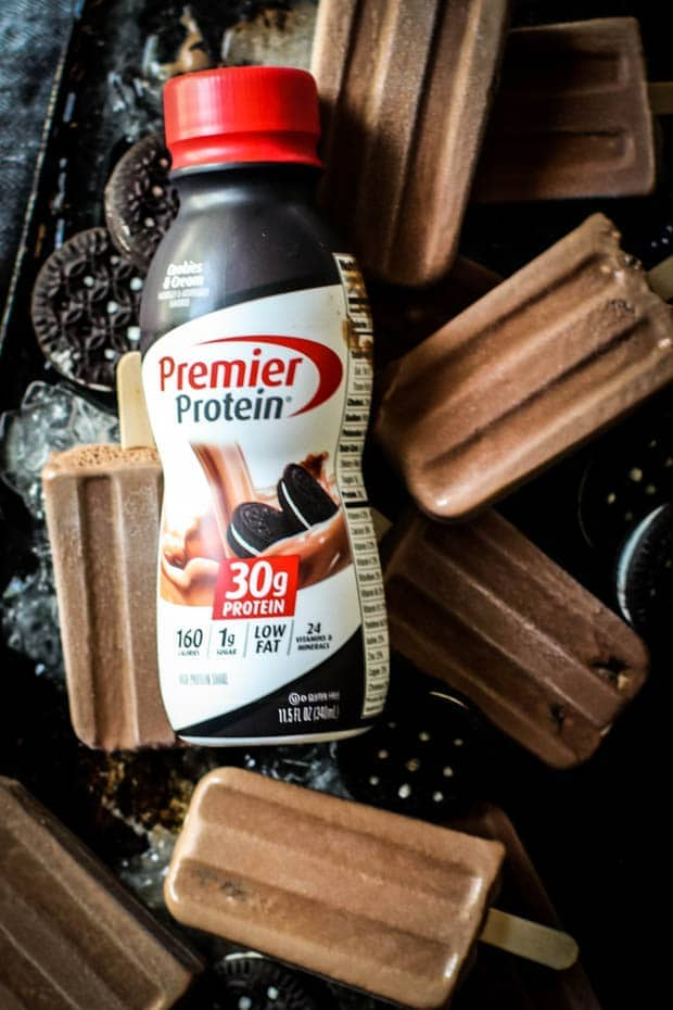 A bottle of Premier Protein Cookies and Cream protein shake is sitting on a tray with fudgesicles and chocolate sandwich cookies.