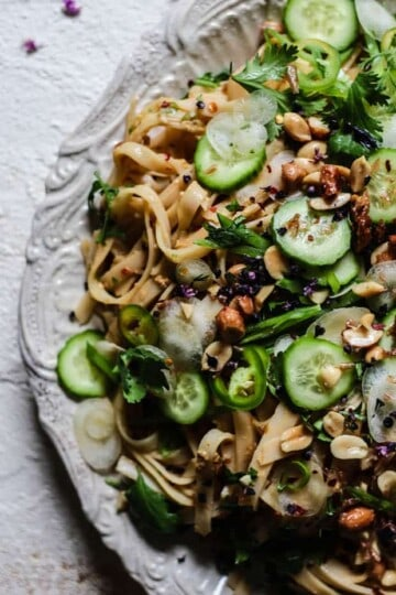 Side crop of a platter of No-Cook Peanut Butter Rice Noodle Salad on an off white back ground - teh =off-white pasta dish is topped with lots of green, crunchy vegetables.