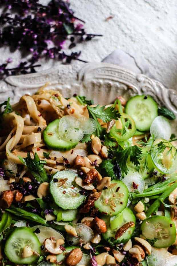The top portion of a very large platter of No-Cook Peanut Butter Rice Noodle Salad. on top of an off white background - the noodles are coated in a rich peanut sauce and topped with lots of crunchy, green vegetables and peanuts.