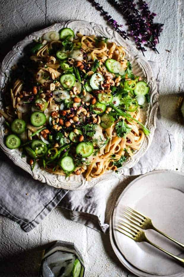 A large, round, off white platter is topped with rice noodles dressed in an Asian peanut sauce then topped with all green vegetables. Thin slices of cucumber, white carrot, snow peas, scallions, jalapeños, cilantro, and red skinned peanuts all garnish teh pasta. There are 2 white plates next to teh platter with 2 forks on them as well as a glass of water with a slice of cucumber.