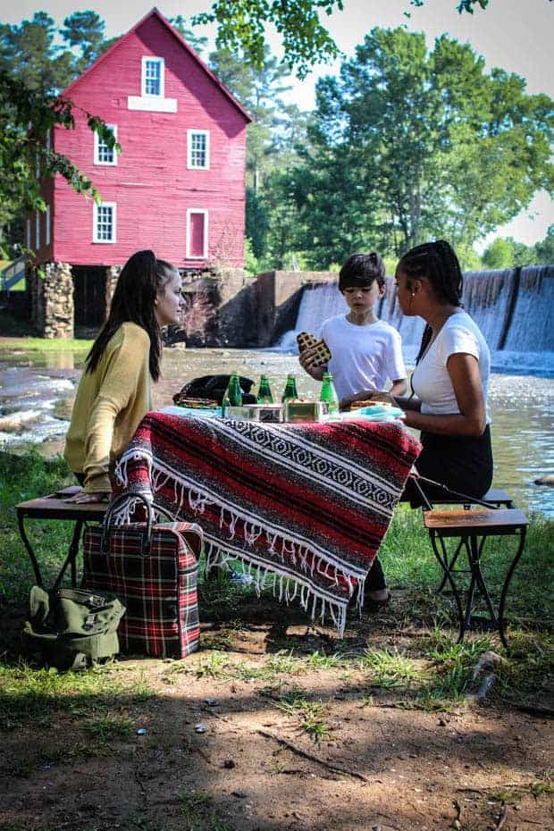 A picnic scene in fort of an old red saw mill with a water fall. There are 2 teenage girls and a small bowl at a pop up picnic table enjoying sandwiches and a game.