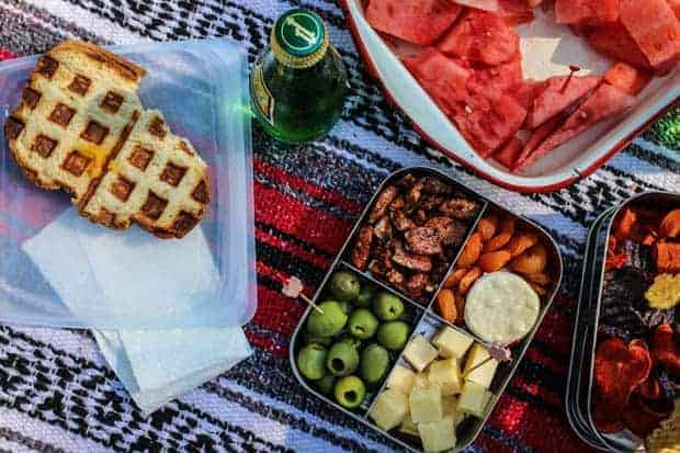 A waffled grilled cheese, a bento box filled with green olives, ,candied pecans, crackers, and Tillamook cheese cubes.
