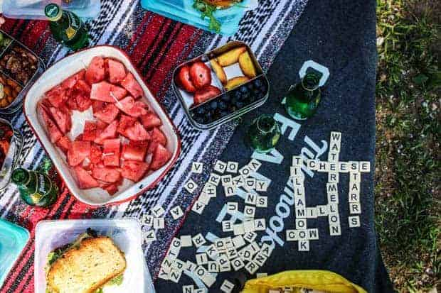 A picnic table is set up with sandwiches, watermelon, sliced fresh strawberries and peaches, and a game of bananagrams.