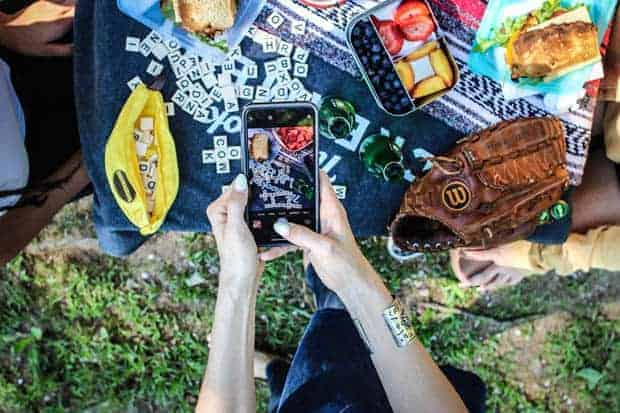 a woman taking a picture of a picnic scene with her iphone, shows vegetarian sandwich recipe