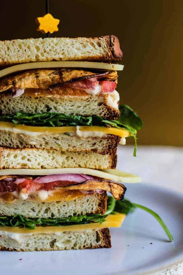 Close up image of 2 ultimate vegetarian club sandwiches staked on top of each other. It layers like this; br4ead, white bean hummus, cheddar cheese, arugula, bread, white bean hummus, yellow and red heirloom tomato slices, eggplant bacon slices, a slice of white cheddar cheese and another slice of bread.