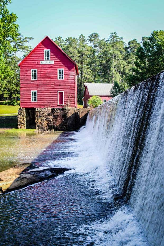 Starrs Mill red saw mill sits next to a water fall.