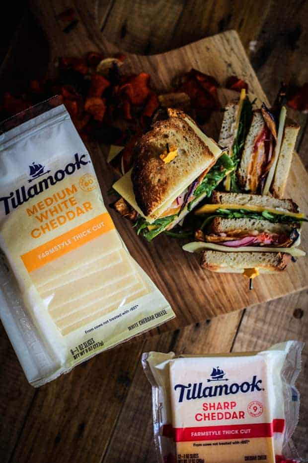 A pile of vegetarian club sandwiches are stacked on a wooden board. There are 2 packages of Tillampook cheese next to the sandwiches.