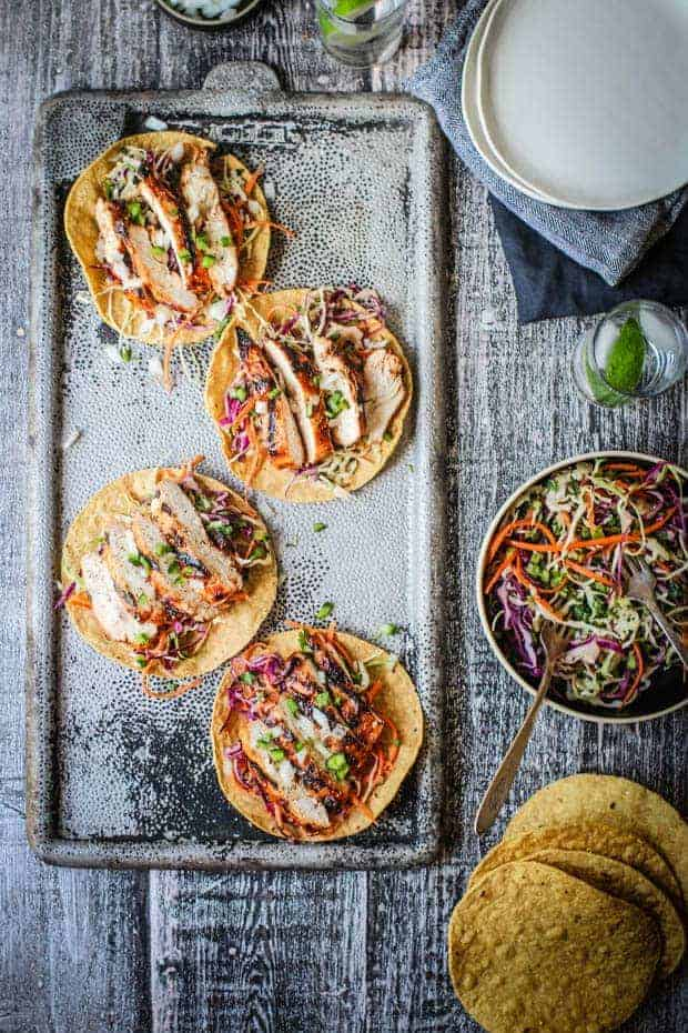 4 BBQ Chicken tostadas on a metal tray on top of a table. The table is set with white plates, glasses of water with lime wedges, extra tostadas, and a bowl of tex-mix rainbow slaw