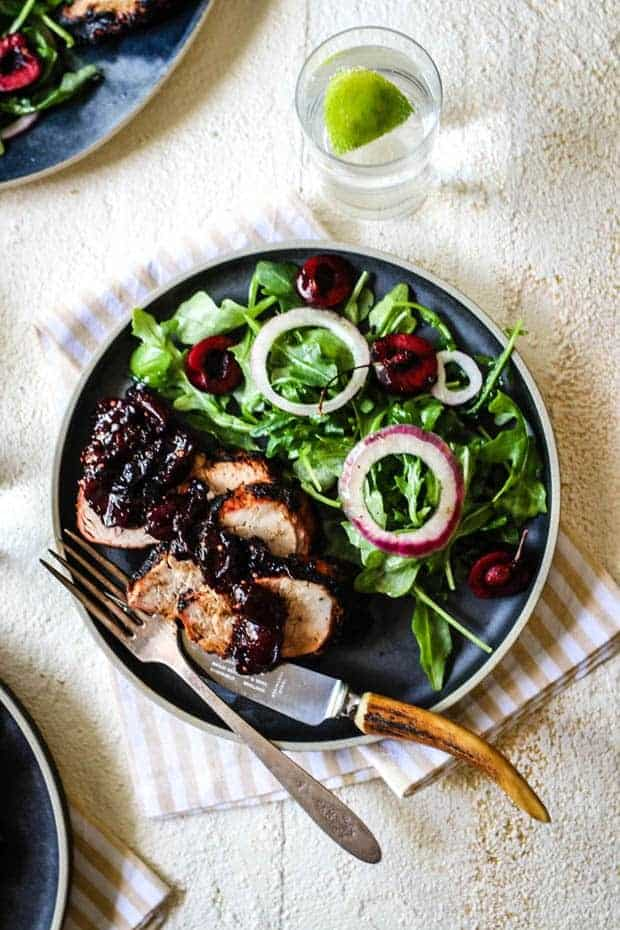 A black plate sits on a white table top over a pale cream and white striped cloth napkin. The plate has an aural salad with marinated red onion rings and fresh cherry halves. There are 3 slices of grilled pork tenderloin on teh plate topped with cherry ginger chutney.